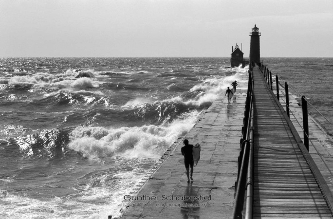 Grand Haven Lighthouse Stormy weather and high winds are not enough to stve off a couragous group a Surfers, ready to navagate the high waves crashing on the dock. 35mm Black and White Film